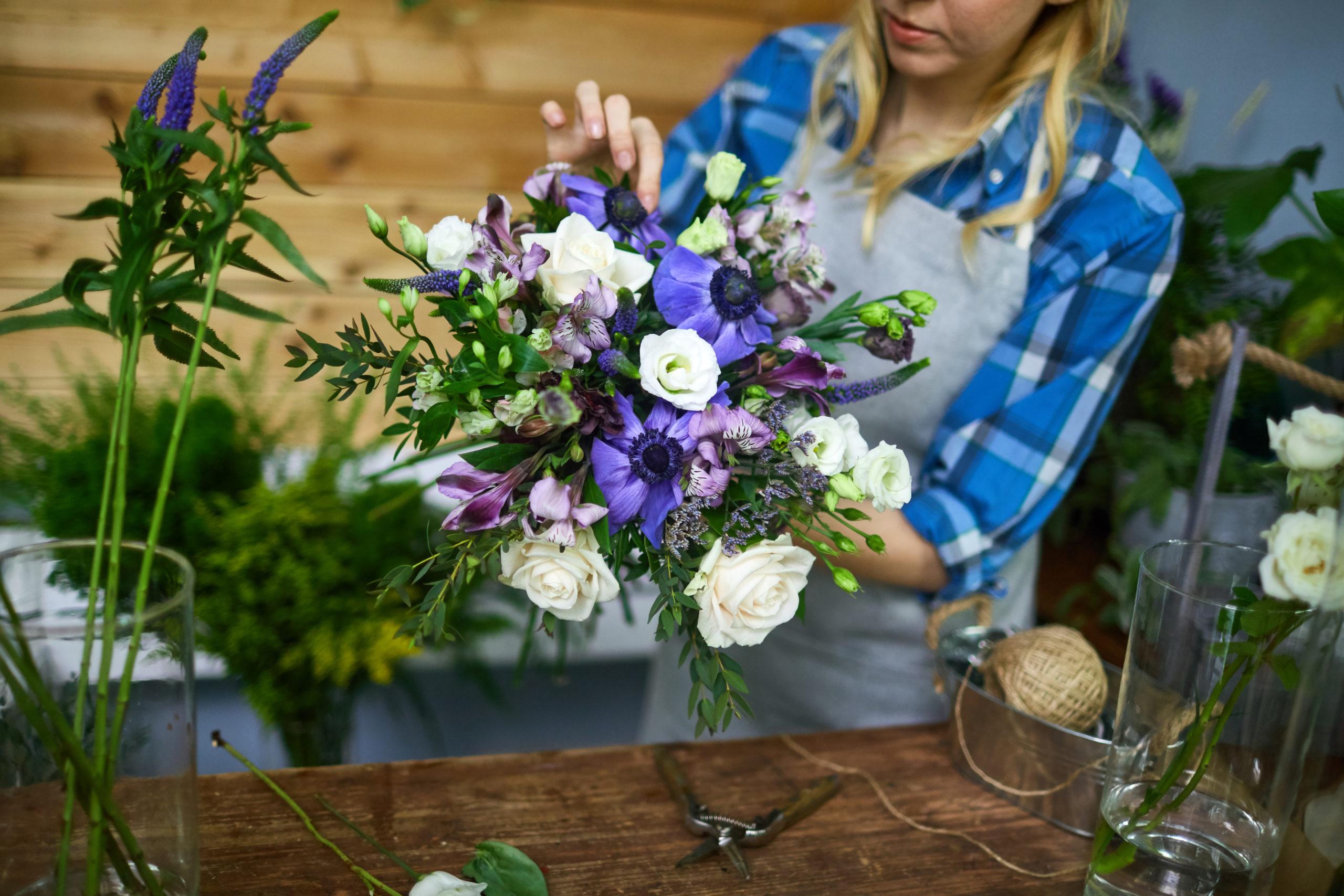 Young woman arranging floral bouquet